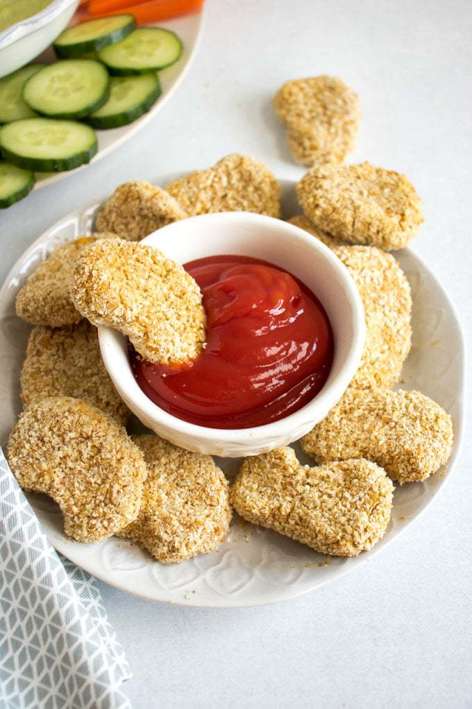 Baked vegan chicken nuggets (an easy 6 ingredient, 30 minute, soy free recipe). A plate of chickpea nuggets with a bowl of ketchup.
