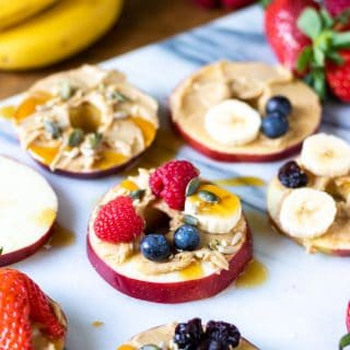 Apple pizzas. This healthy snack is really easy. Slices of apple are spread with peanut butter and topped with fruit and seeds, with a little drizzle of maple syrup. Get the heathy snack recipe now.