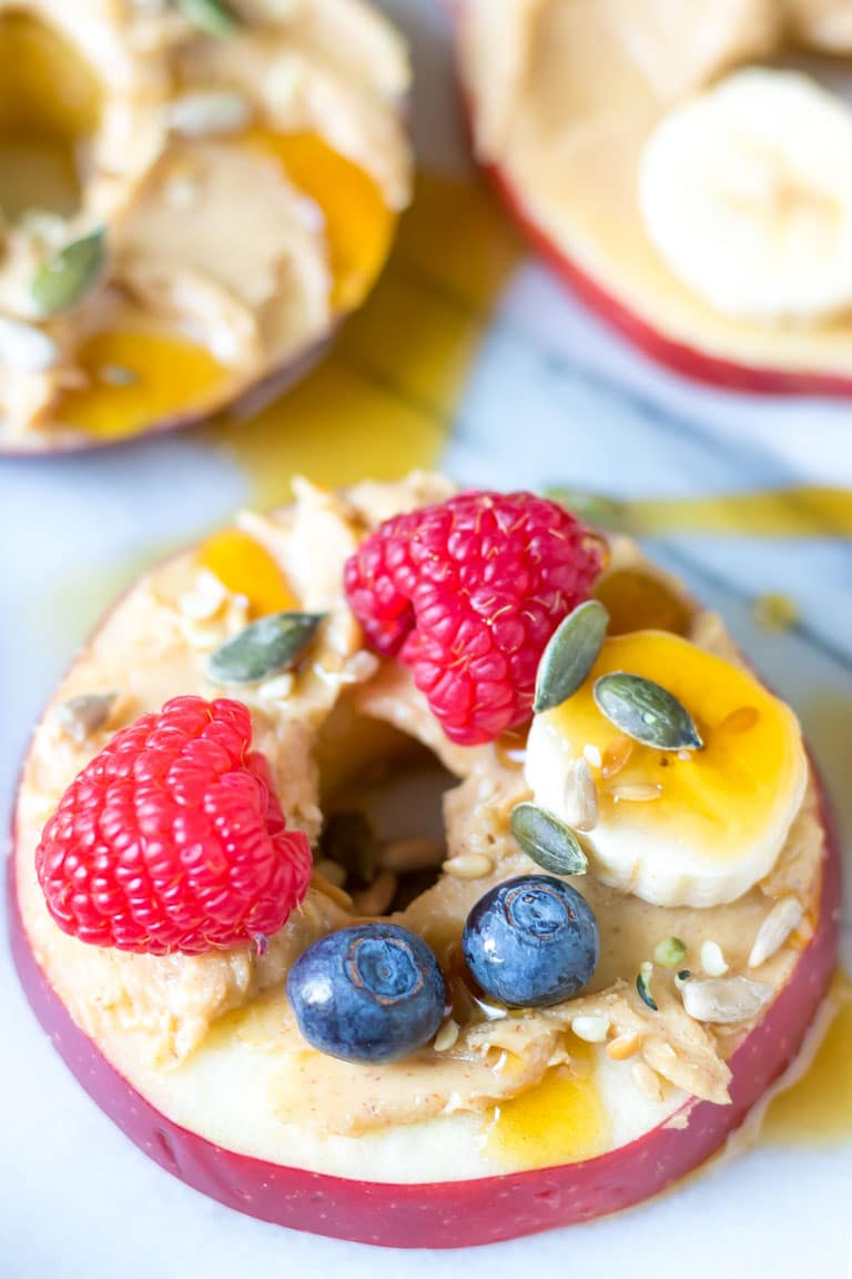 Close up of an apple ring topped with peanut butter, fruit and seeds.
