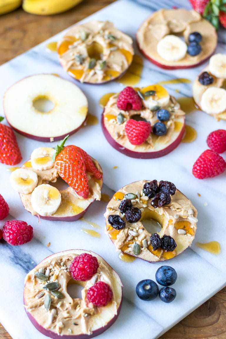 Slices of cored apple spread with peanut butter and topped with fruit, seeds and maple syrup. Vegan kids snack recipe.