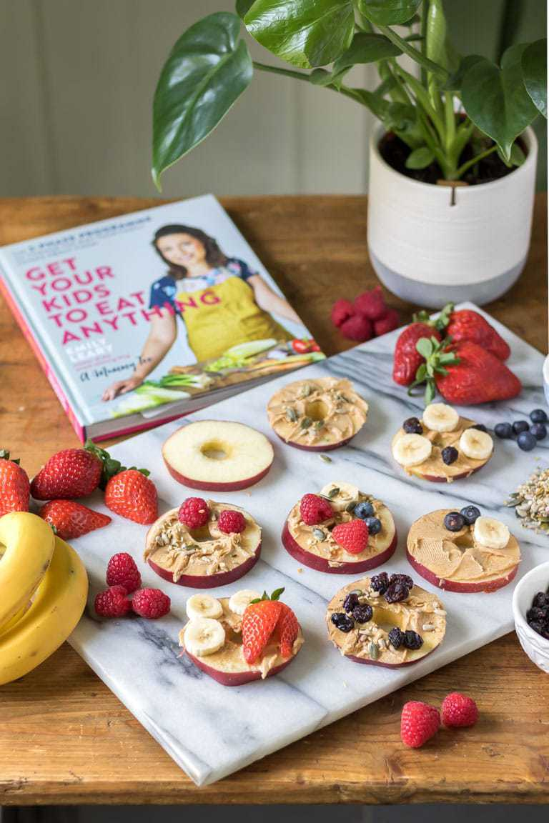 A tray of apple pizzas, slices of apple with peanut butter, fruit and seeds. An easy health snack idea for kids. Get the recipe.
