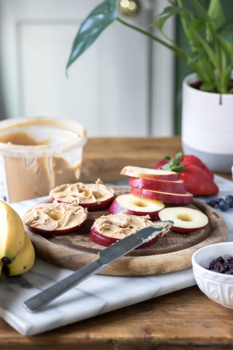 Apple pizzas - healthy snack ideas. A chopping board with slices of apple being spread with peanut butter. Get the easy recipe now.