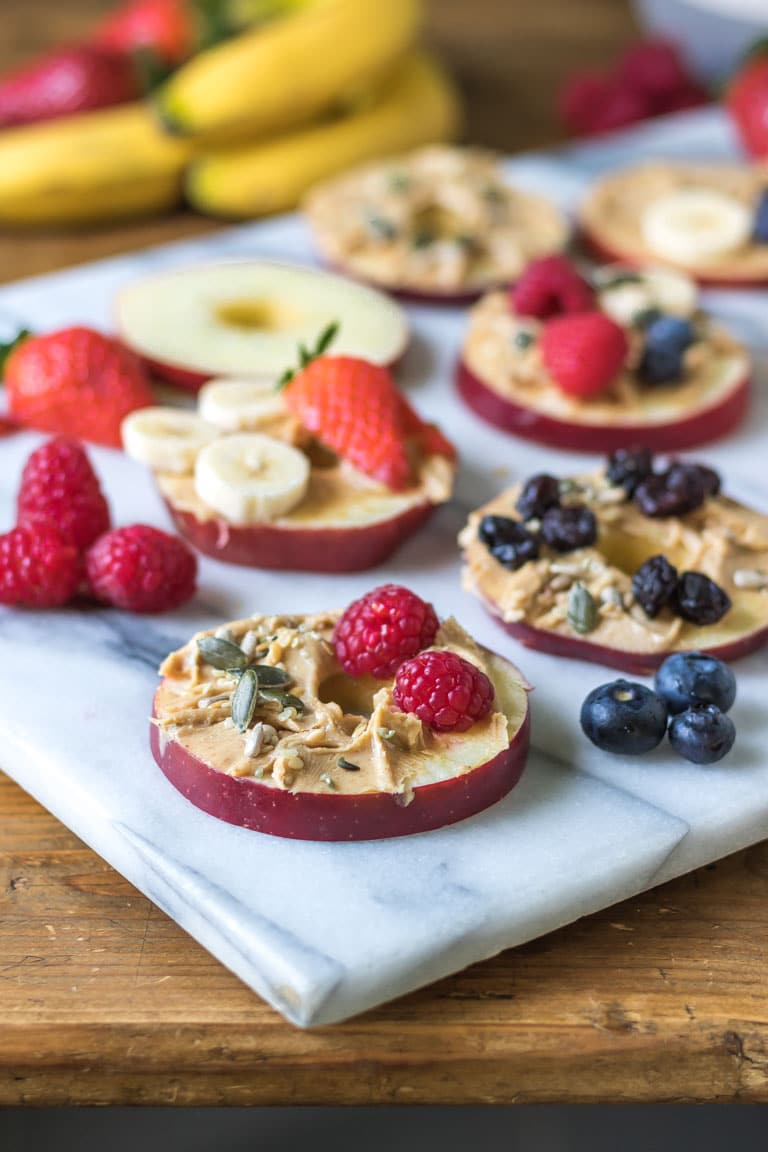 Round slices of cored apple are shown on a marble board spread with peanut butter and topped with fruit and seeds. Get the easy snack recipe now.