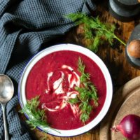 A bowl of creamy beetroot soup on a wooden table with sprigs of fresh dill.