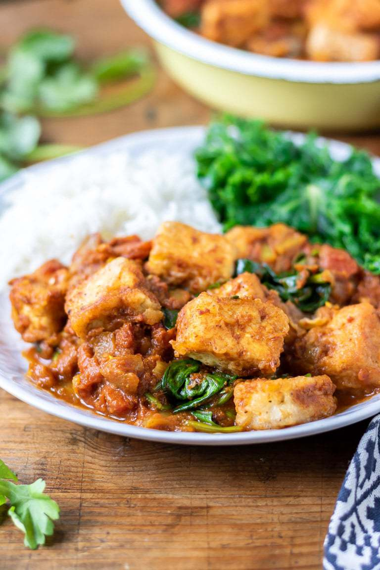 Tofu curry on a plate with steamed kale and rice. In this vegan curry recipe, the tofu is fried until crispy then added to the fragrant sauce with Indian flavours.