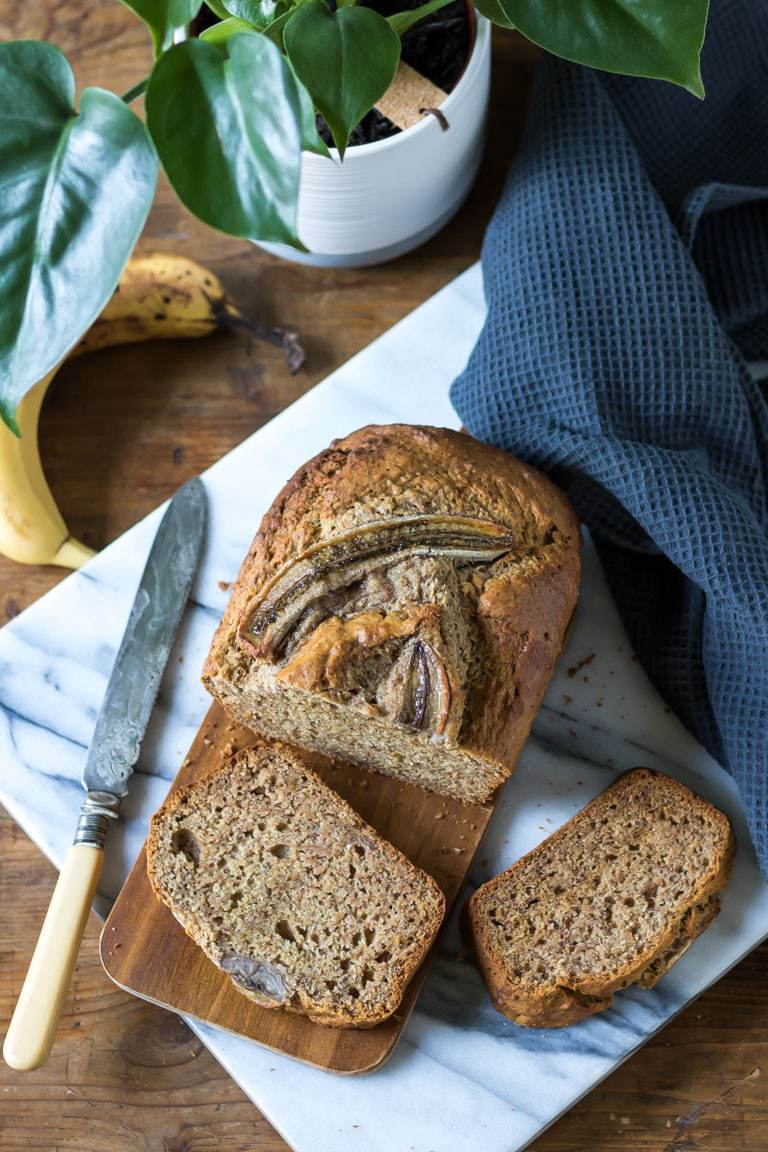 Moist and easy one bowl vegan banana bread with slices cut out next to a banana and plant. Get the recipe.
