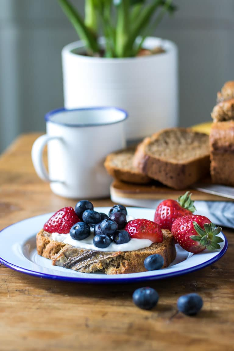 A thick slice of moist and easy vegan banana bread with dairy free yogurt and berries. Get the easy one bowl 10 ingredient recipe now.