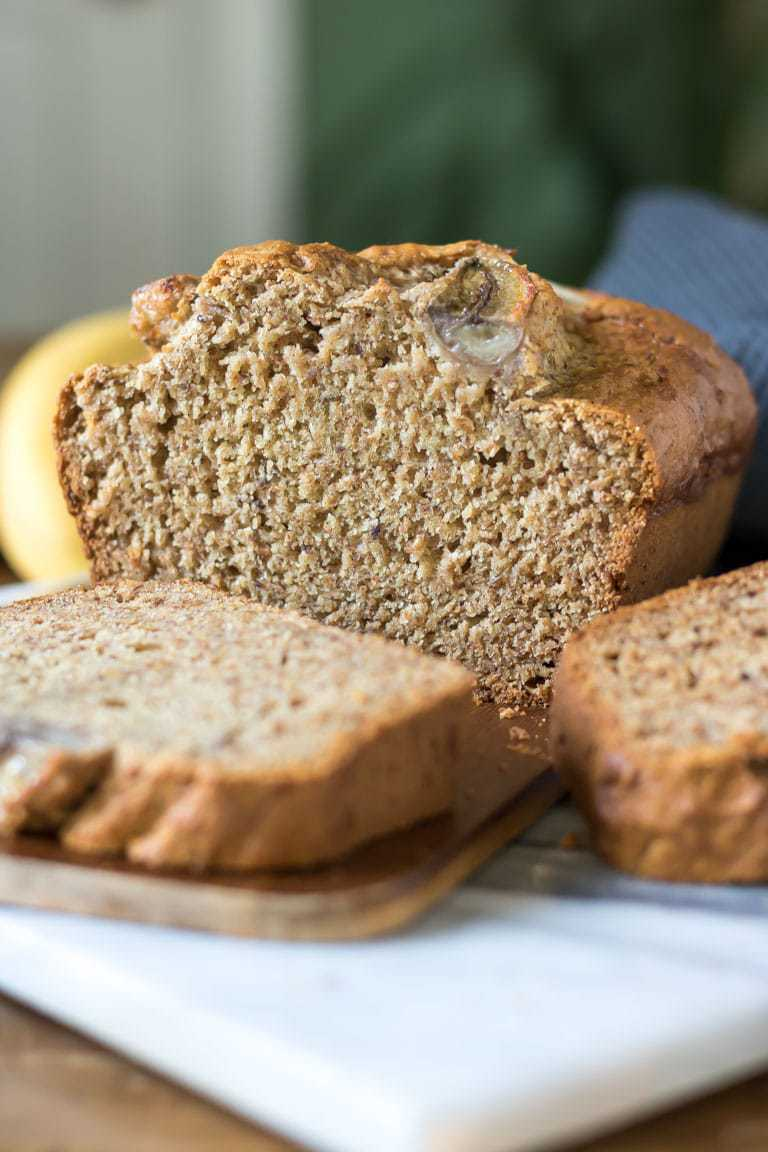 Close up of a slice of moist and delicious vegan banana bread. Slices of the tasty cake have been cut from the loaf. Get the easy one bowl recipe now.
