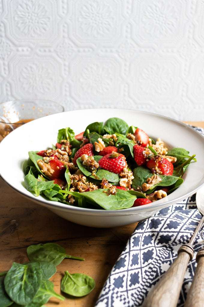 A bowl of salad with spinach, strawberries and walnuts on a wooden table in front of a white wall. The vegan salad has a toasted seed, balsamic and maple syrup dressing to bring out the flavor of the spinach and strawberries. Ready in just 15 minutes. Get the recipe now.