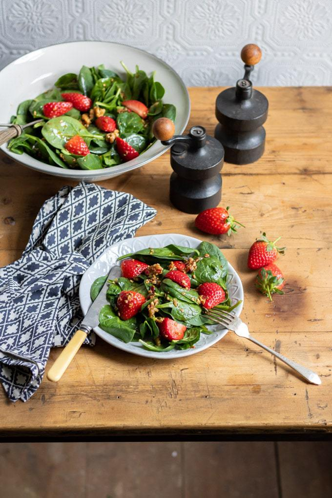 A table laid with a big serving bowl of spinach salad. Next to a blue napkin, a plate is pile with strawberry spinach salad and topped with walnuts. Get the easy spinach salad recipe now. It only takes 15 minutes and tastes great.