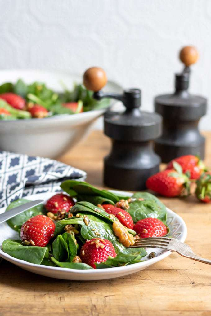 A bowl of strawberry spinach salad on a table. The vegan salad is topped with walnuts and a toasted seed dressing with balsamic and maple syrup. It's ready in just 15 minutes and tastes delicious. Get the recipe.