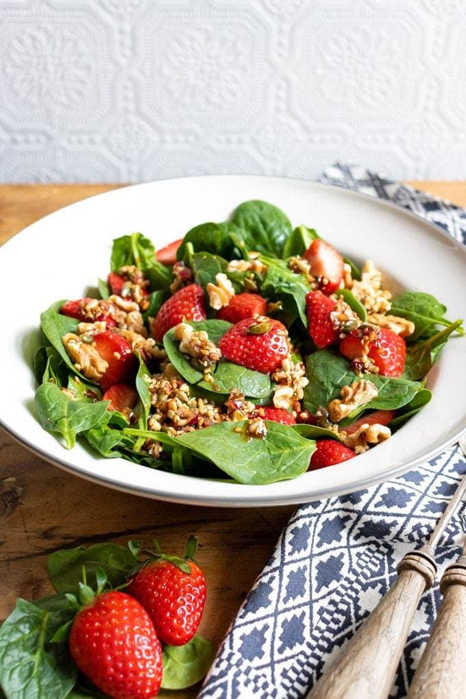 A bowl of colorful tasty strawberry spinach salad with walnuts and a 5 ingredient toasted seed dressing with balsamic and maple syrup. Vegan recipe.