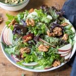 Close up of an apple walnut salad drizzled with a tasty walnut pesto dressing. It's then sprinkled with easy rosemary maple glazed walnuts. It's a delicious vegan salad recipe..