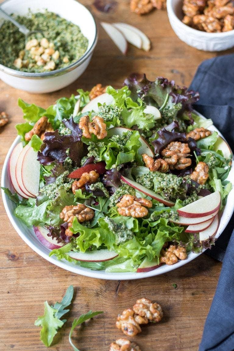 Table with a salad full of walnuts, apples and lettuce.