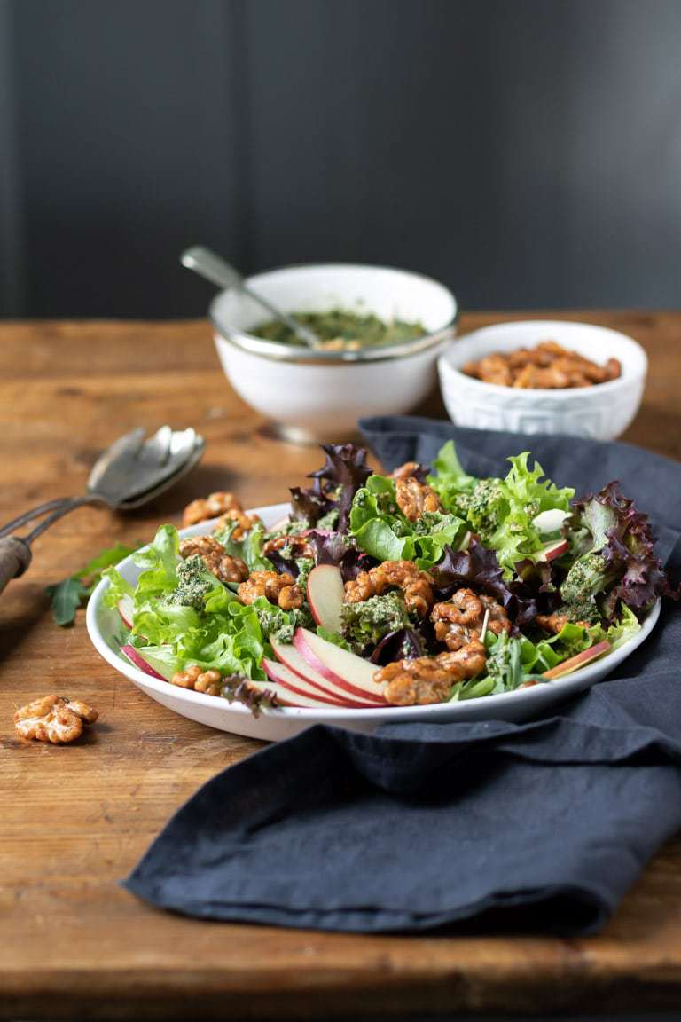 A wooden table with a plate of apple walnut salad, drizzled with walnut pesto and sprinkled with maple glazed walnuts.