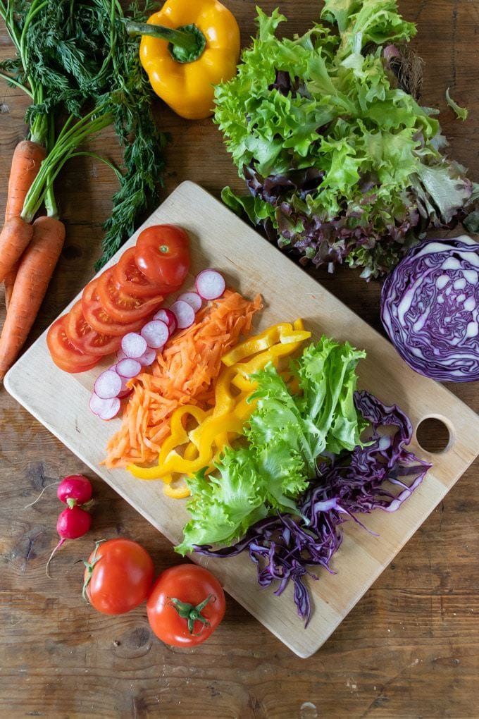 A table with vegetables sliced for a sandwich, including tomato, radishes, carrot, yellow bell pepper, lettuce, cabbage and more.