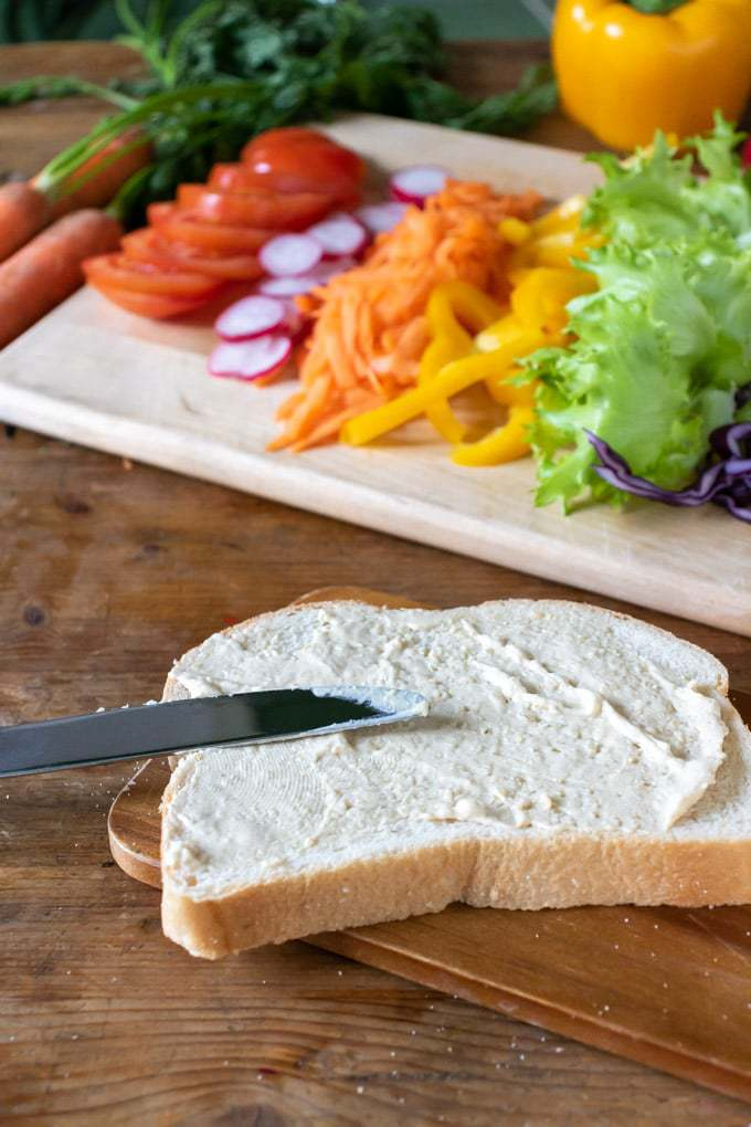 How to make a vegetable sandwich - spreading the bread with hummus in front of a tray of sliced veggies.