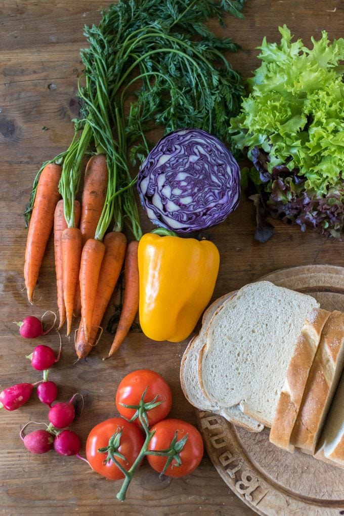 Flat lay of fresh veggies for a rainbow sandwich full of veggies. Next to slices of fresh bread.