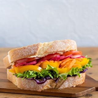 Wooden tray with a vibrant vegan rainbow veg sandwich. Layers of fresh, crunchy raw vegetables include cabbage, carrot, tomato and more. Get the vegan sandwich recipe.