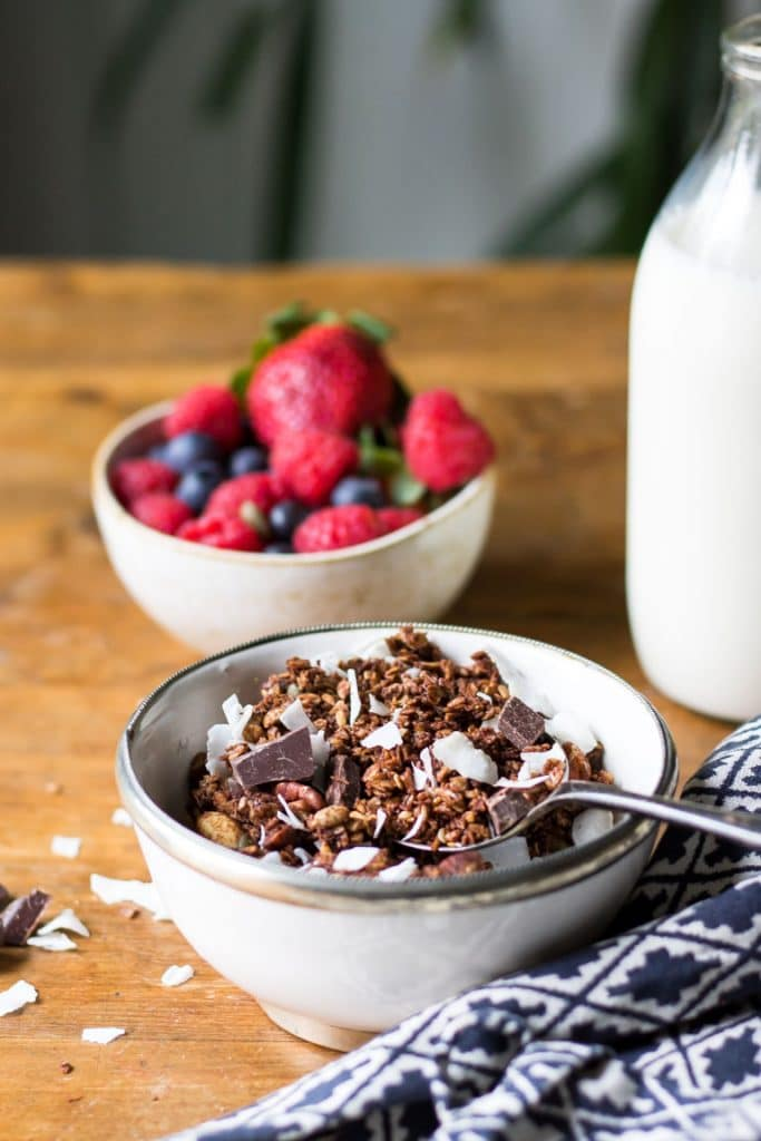 A bowl of homemade granola. The vegan granola with chocolate and coconut is shown in front of a bowl of berries.