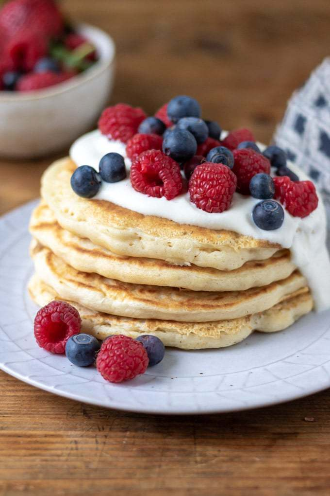 A stack of easy vegan pancakes with coconut yogurt and fresh berries