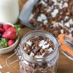 Looking down into a jar of homemade granola with chocolate and coconut. A healthy vegan breakfast.
