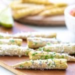 Close up of a mini elote Mexican Street corn made with baby corn. Shown sprinkled with parmesan and herbs.