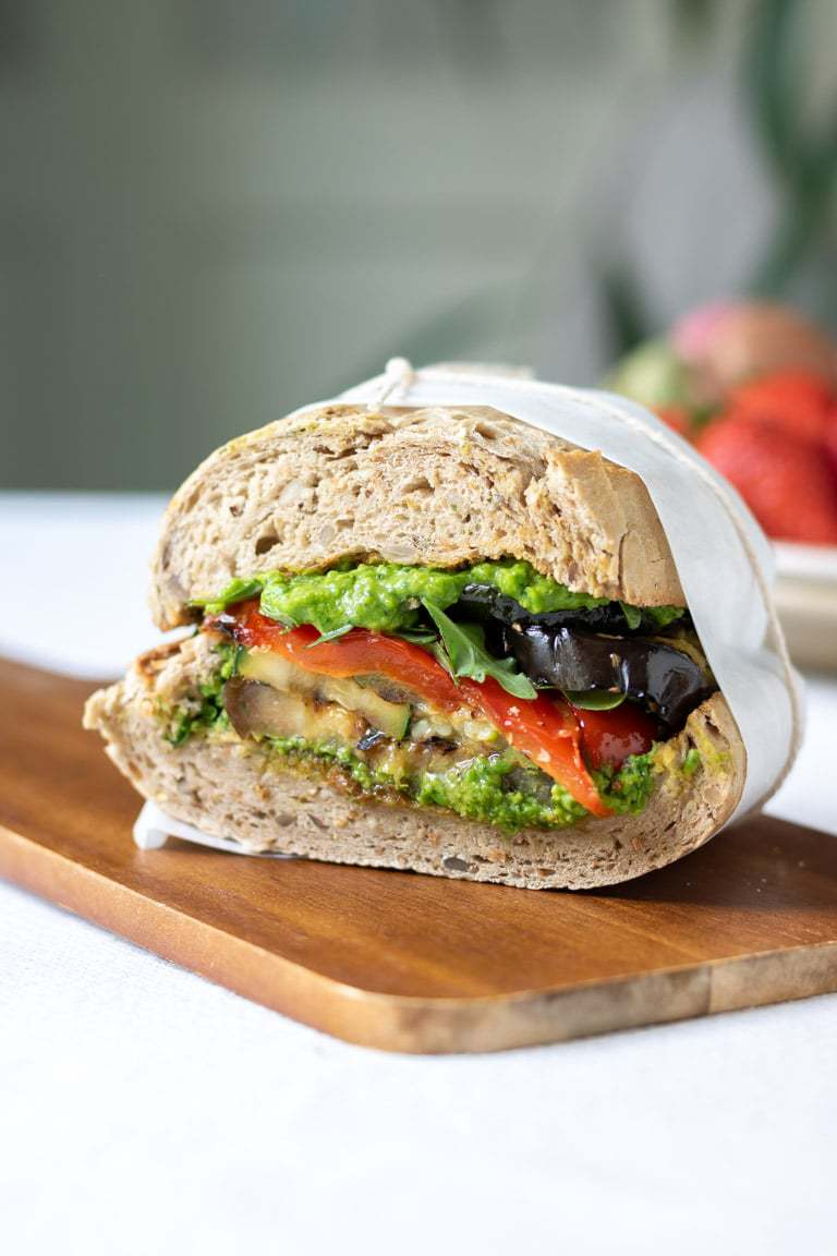 Close up of a cut roasted vegetable sandwich with pea pesto on a wooden board.