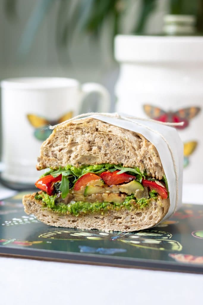 Close up of a roasted vegetable sandwich wrapped in paper and tied with string