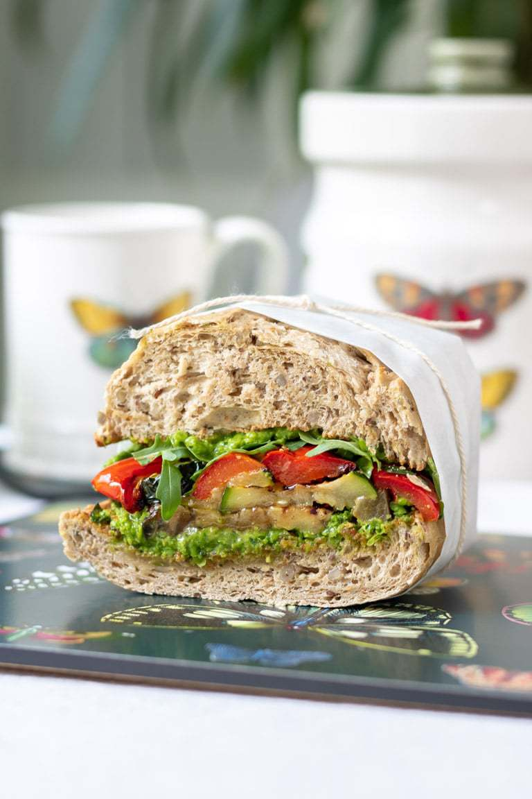 Close up of a roasted vegetable sandwich wrapped in paper and tied with string.