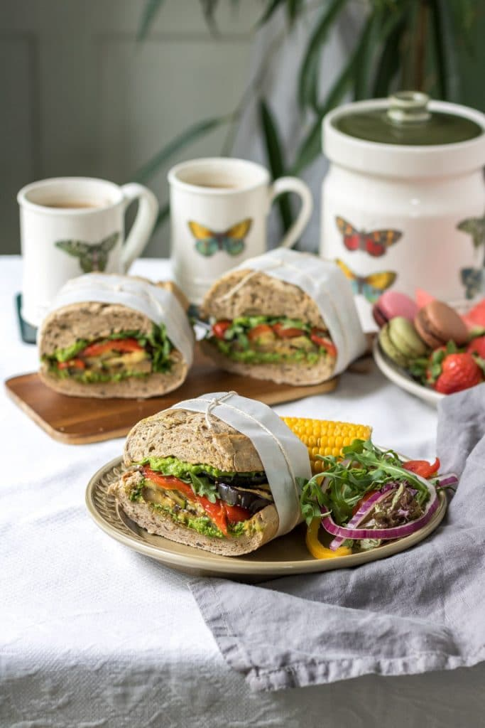 Roasted vegetable sandwiches wrapped in paper and string on a table laid for a picnic with salad, tea cups and macarons.