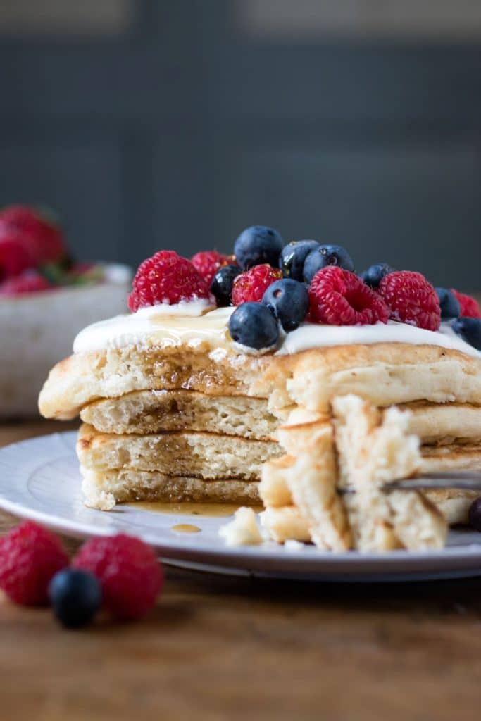 A stack of fluffy vegan pancakes made with no banana or unusual ingredients. Shown with yogurt and berries.