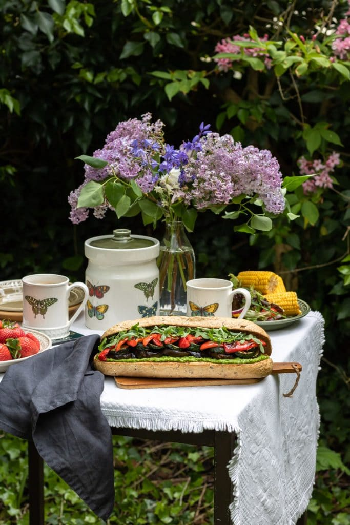 A roasted vegetable sandwich on a picnic table in the backyard, with tablecloth, pretty butterfly crockery and flowers.
