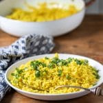 A serving bowl of yellow rice (turmeric rice recipe) topped with fresh herbs, shown with a vintage serving spoon and blue napkin.