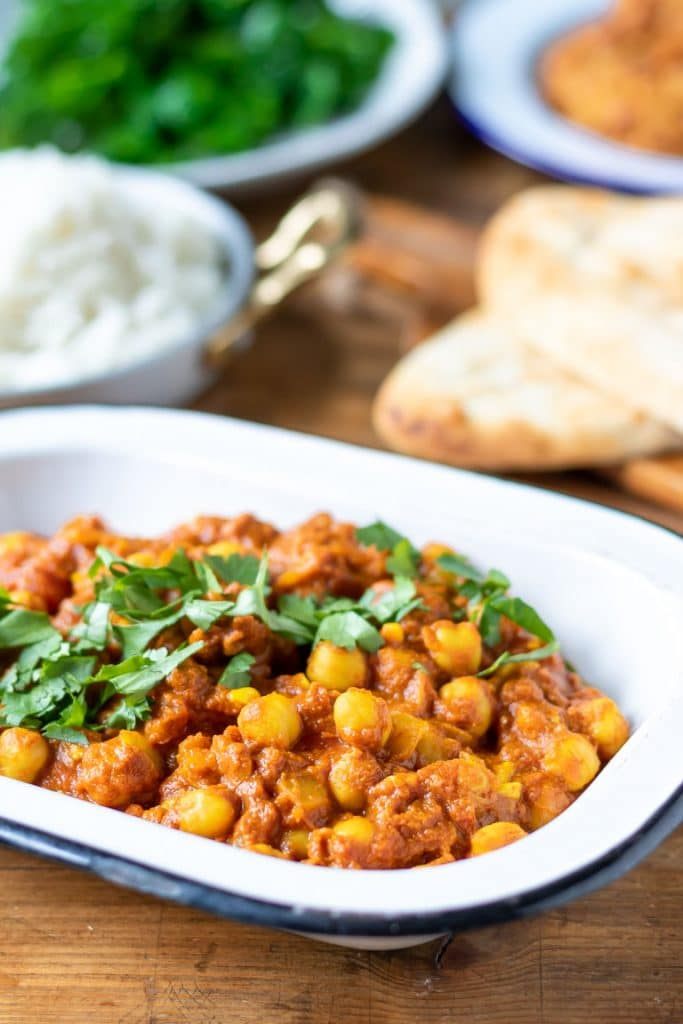 A serving bowl full of easy and tasty chickpea curry. The vegan Indian recipe is easy to make in 20 minutes. Shown in front of dishes of rice, steamed kale and naan.
