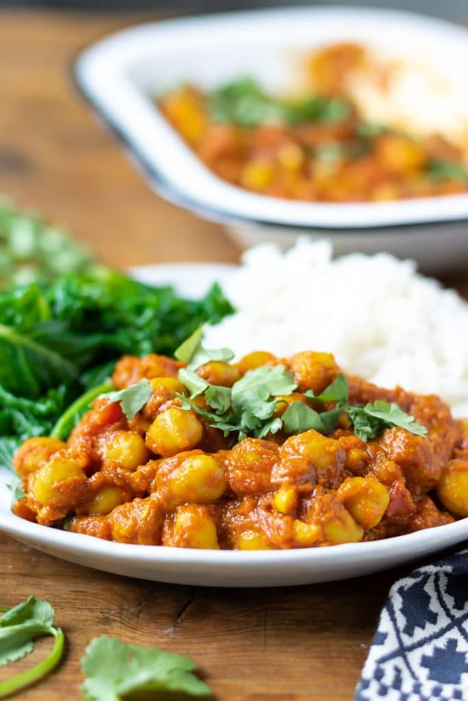 Close up of a plate with chickpea curry. The vegetarian indian recipe is served with steamed kale and rice. Shown with serving dish of the vegan chickpea curry in the background.