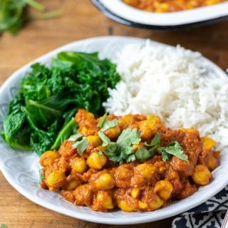 A plate of delicious vegan chickpea curry, shown with rice and steamed kale. 20 minute recipe.