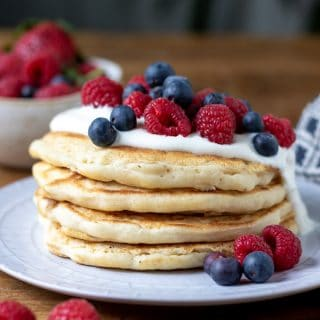 A stack of fluffy dairy free pancakes (vegan, eggless) vegan yogurt and fresh berries.