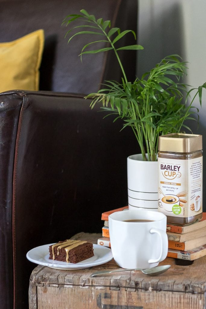 A plate with a Barleycup brownie and a mug and jar of Barleycup next to a plant on an end table