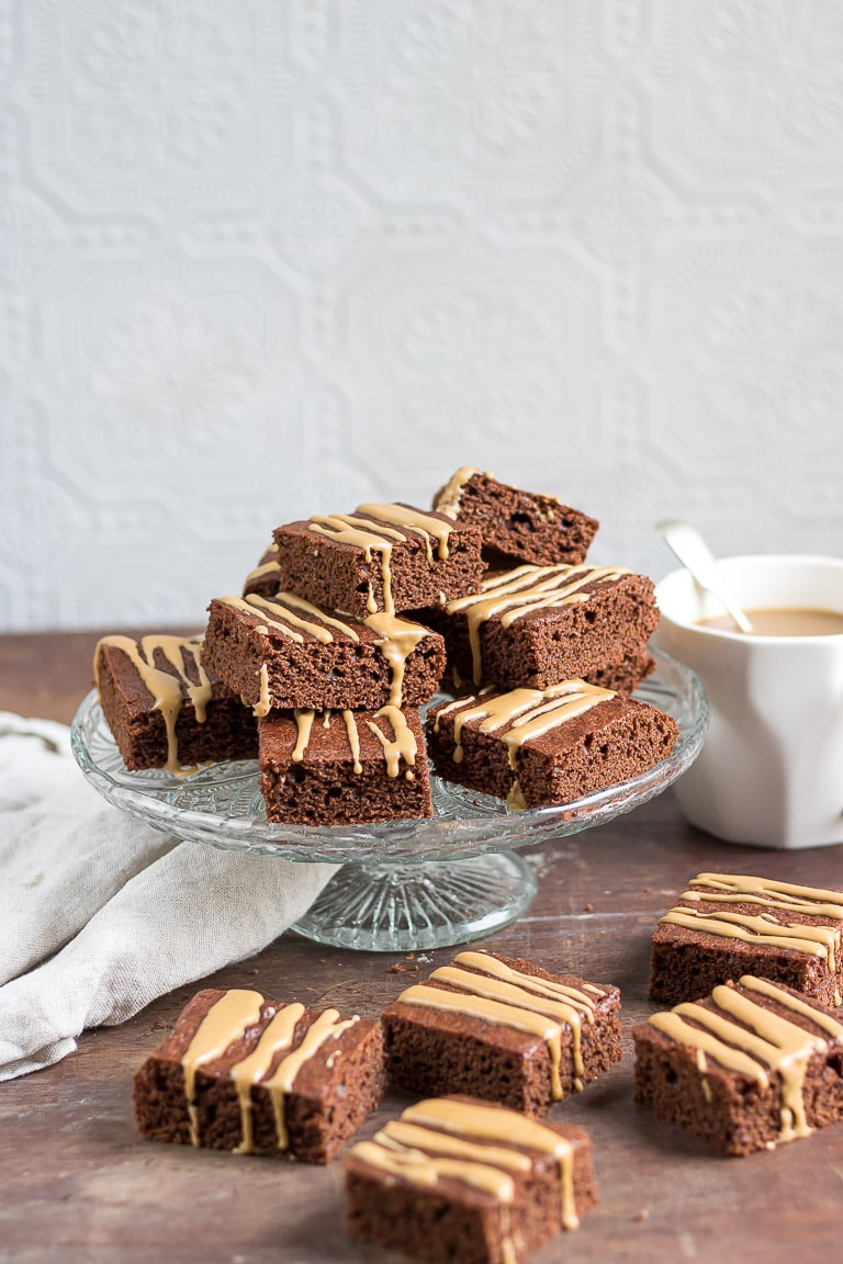 A vintage glass cake stand with Barleycup brownies piled onto it with a few brownies scattered around.