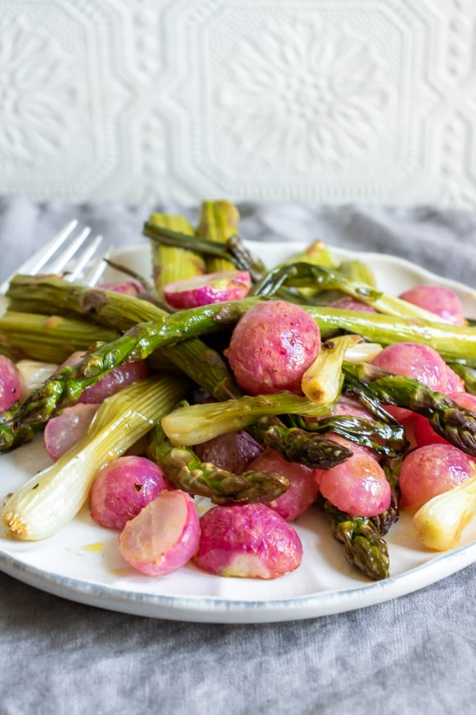A white plate on a grey napkin, with roasted asparagus and radishes with a maple dijon dressing