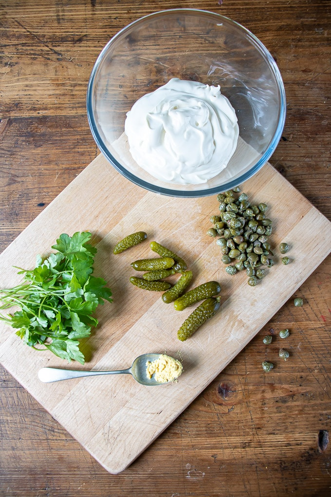 Tartare sauce ingredients - a bowl of mayo, with chopped capers, pickles gherkins, parsley and a spoon of mustard powder.