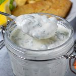 A spoonful of homemade tartare sauce coming out of a jar, next to a plate of fish and chips.