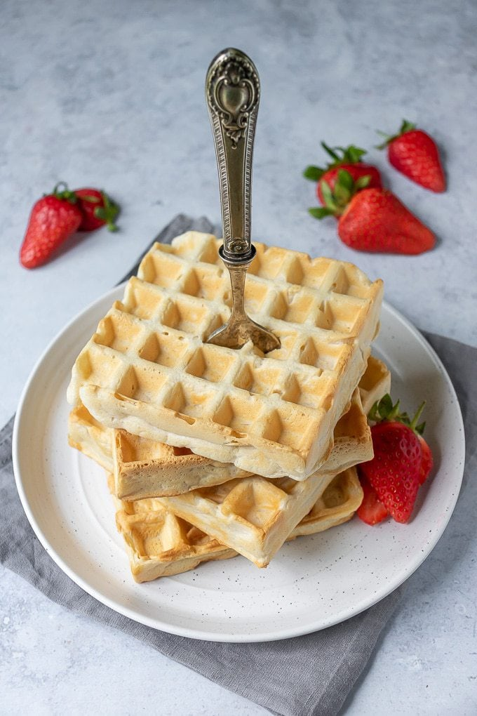 A stack of easy fluffy vegan waffles on a white plate with a vintage fork stuck down through the stack. With strawberries on the side.