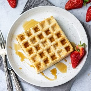 A white plate with eggless waffle recipe drizzled with maple syrup and strawberries on the side.