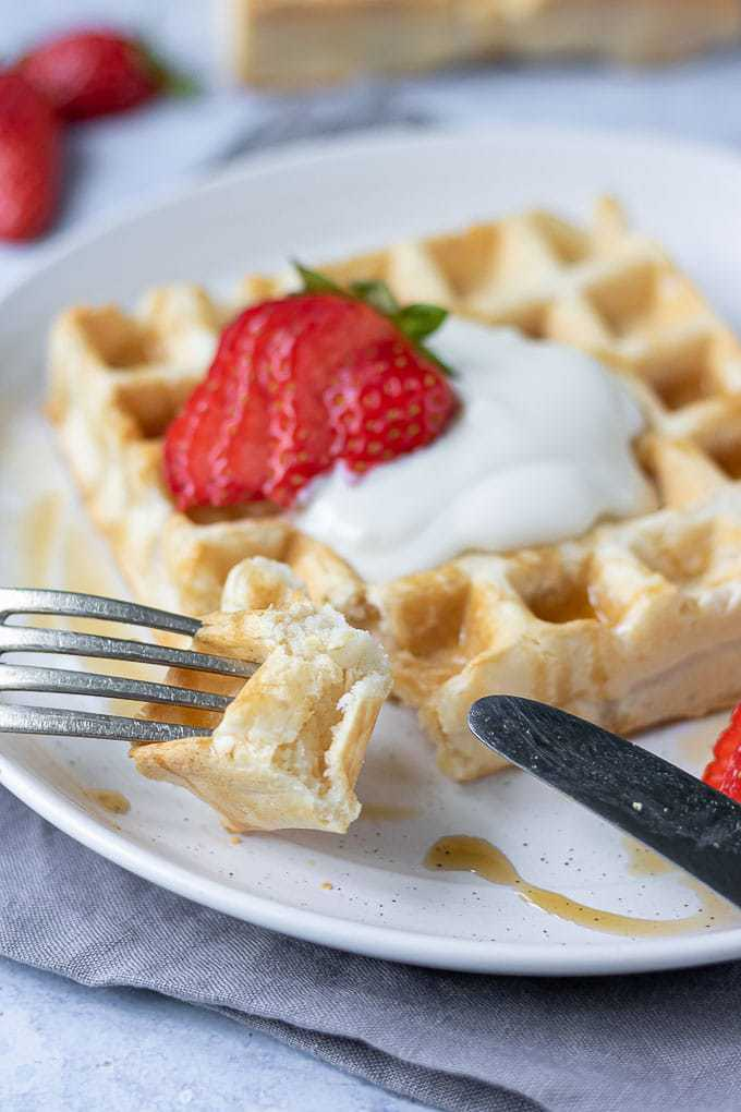 Close up of a fork with a piece of fluffy vegan waffle, topped with dairy free yogurt and strawberries.
