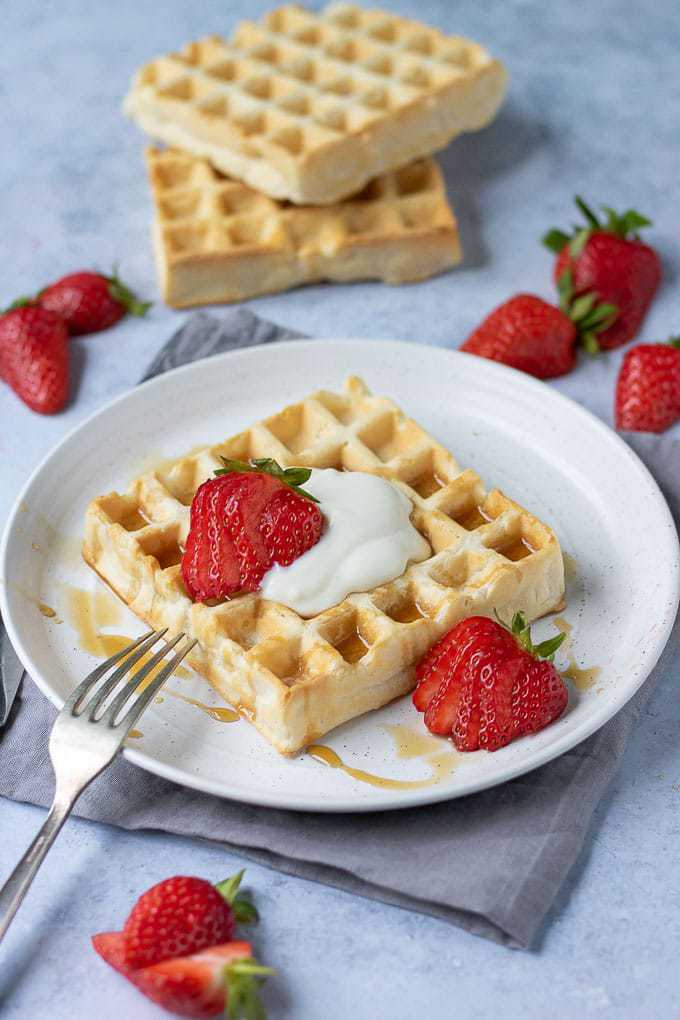 A white plate with an easy vegan waffle drizzled with maple syrup and topped with dairy free yogurt. The eggless waffle recipe is also shown with strawberries.