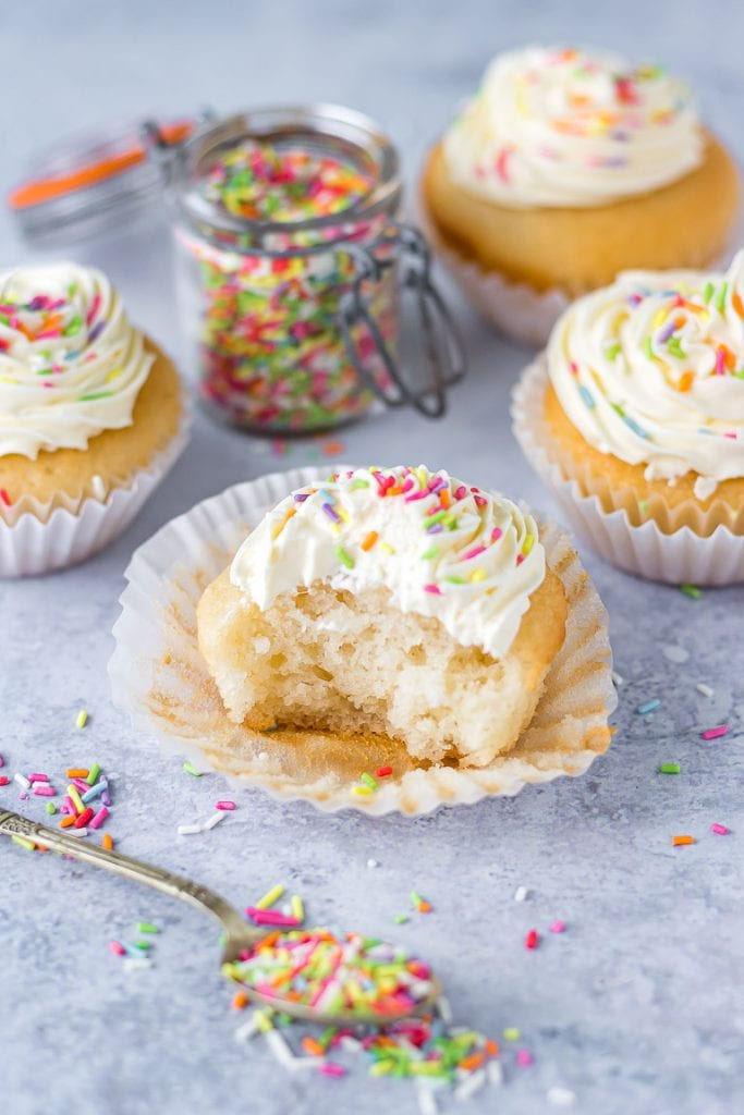 A vegan cupcake with a bite taken out. Covered in vanilla frosting and sprinkles.