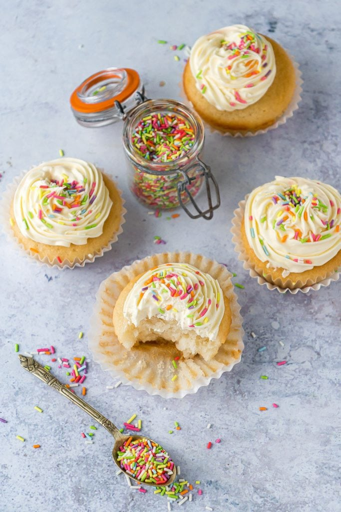 OVerhead shot of vegan vanilla cupcakes with sprinkles, next to a spoonful of sprinkles.