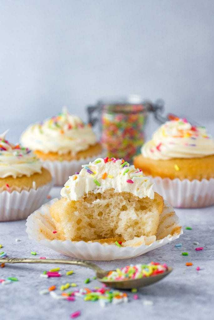 An easy 1 bowl vegan vanilla cupcake with a bite taken out. With a spoonful of sprinkles in front.